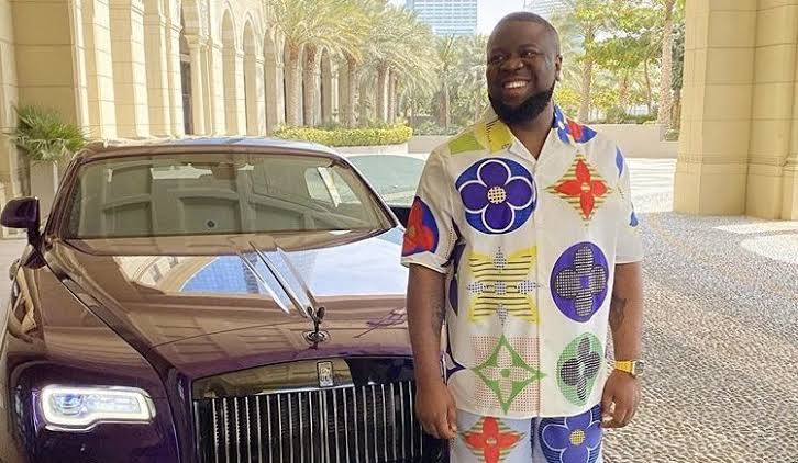 Hushpuppi picture smiling standing next to car